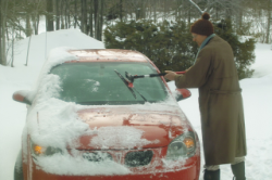 Brushing the snow of the car.