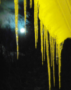 the moon looking in between icicles